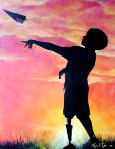 Child with prosthetic leg throwing a paper art plane at dusk.